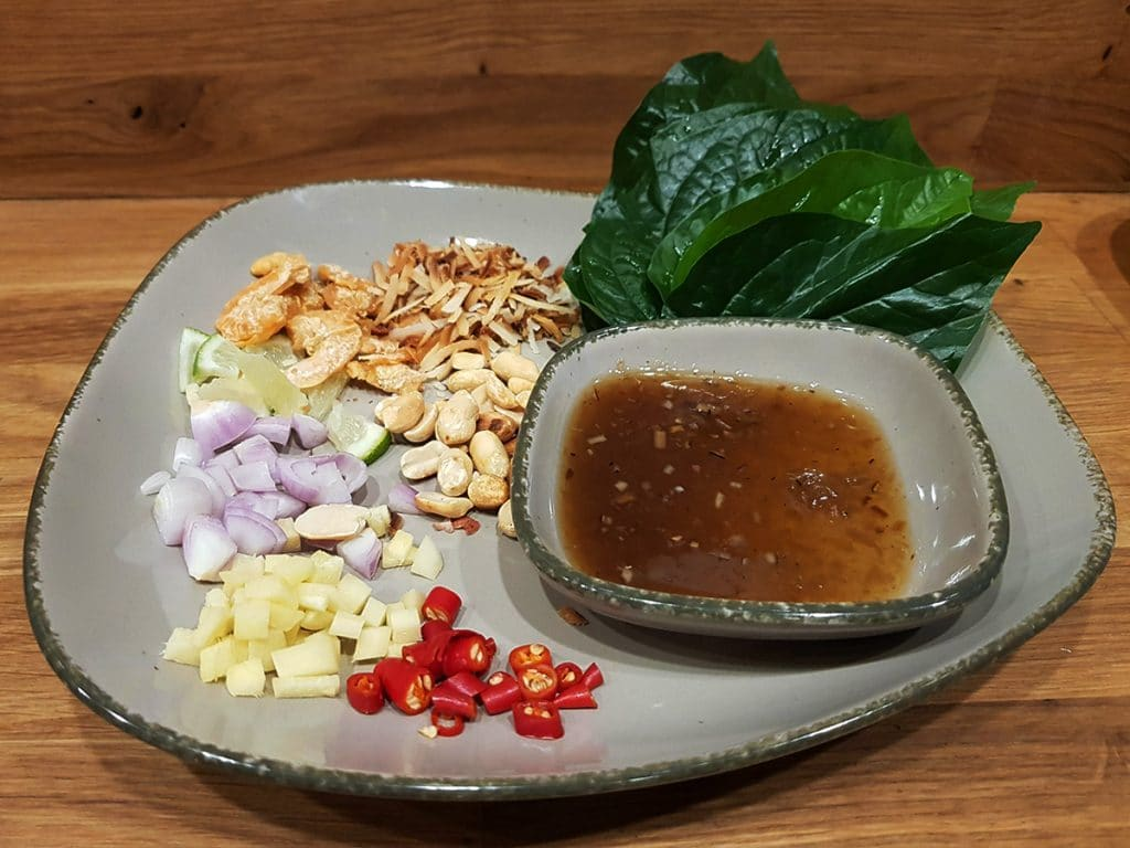 A plate of Thai food Miang Kham, betel leaves, coconut, shrimps, lime, peanuts, onions, ginger and chili.