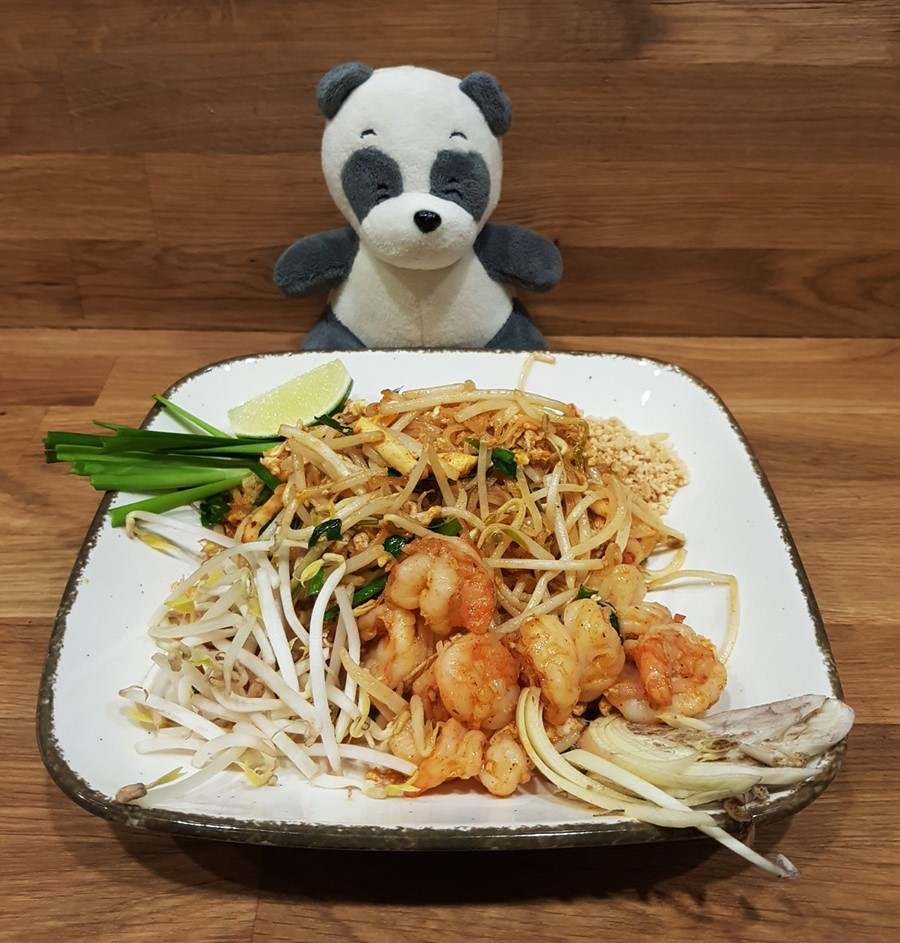 Mister Wong behind a plate of Thai food Pad Thai with shrimps