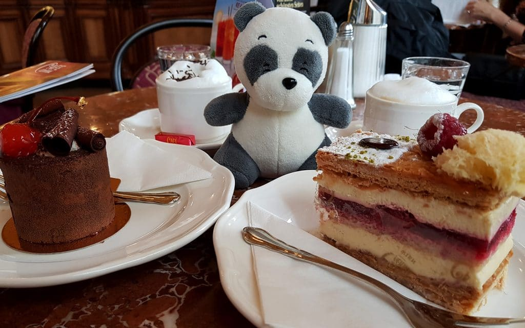 Mister Wong eating Black Forrest Cake and Raspberry Vanilla Cream Cake at Café Central, Vienna, Austria