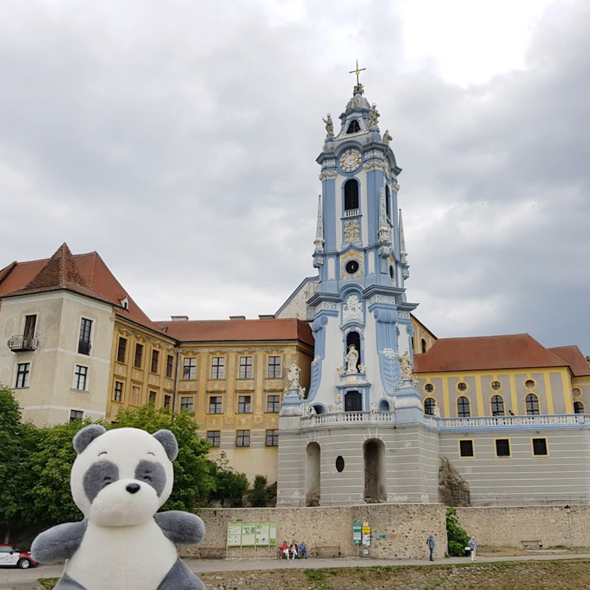 Plush panda Mister Wong looking at the famos clock tower of the church in Dürnstein.