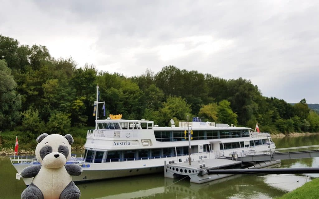 Plush panda Mister Wong in front of a Danube River public-transit ship.