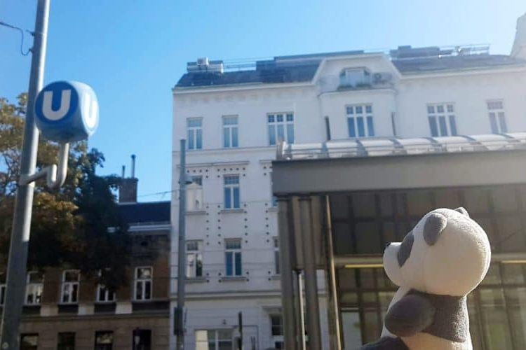 Plush toy Mister Wong looking at the U sign which indicated that there is a Vienna subway station near him.